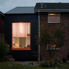 Lipton Plant Architects has updated a 1970s house in Berkshire, England, with a small two-storey extension, featuring a concealed brick-patterned door