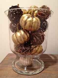 Gold pumpkins in a vase.