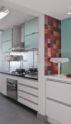 Feito de recortes de papel, esse patchwork inspirou a escolha do refrescante turquesa aplicado na parede
