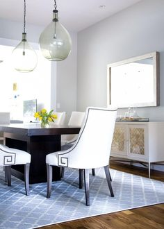 Dining room with large bulb light fixtures, white armchairs with metal details and large artwork