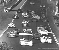 Laguna Seca Can Am, 1966: Phil Hill (65) and Jim Hall (66) lead the field toward Turn 1 at the start of the Laguna Seca Can Am in October 1966. Bruce McLaren (4), John Surtees (7), Denny Hulme (8), Mark Donohue (61), Chris Amon (5), Masten Gregory (88), George Follmer (16), Parnelli Jones (98), and Dan Gurney 36 are among those giving chase.