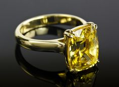 6.06 carat unheated yellow cushion cut sapphire in custom yellow gold split claw prong solitaire setting