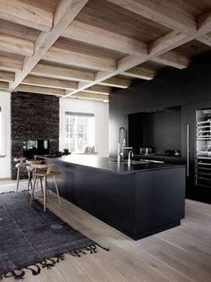 intérieur minimaliste, îlot de cuisine noir, chaises de bois, plafond en bois http://amzn.to/2keVOw4