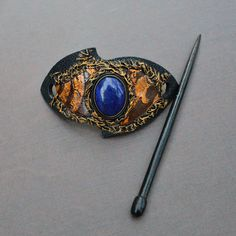 "Handmade barrette from leather with natural Lapis Lazuli stone .   Barrette is 5 x 10 cm (2"" x 4"") and wood hair stick is 15,5 cm ( 6,1"") in length.  Materials: leather, wood ( stick), Natural Labradorite stone .    In ancient times Lapis Lazuli was most highly regarded because of its beautiful color and the valuable ultramarine dye derived from it. Its name comes from the Latin lapis, ""stone,"" and the Persian lazhuward, ""blue."" Its deep, celestial blue remains the symbol of royalty and…"