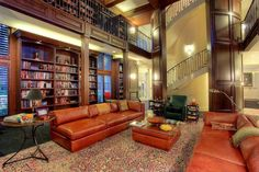 Stunning, two story library room features expanse of floral patterned rug, with red leather sectional sofas mirrored with matching square cushion topped ottoman featuring glass table surface in between.