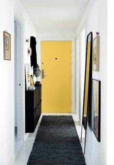 While this hallway appears too tight for storage, a slim wall-mounted shoe rack keeps shoes out of sight and off the floor.