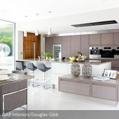 Diese Küche wurde in Weiß und Taupe gestaltet und schafft so eine moderne und dennoch zurückhaltende Atmosphäre. Coole Elemente wie die grauen Barhocker…