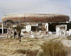 David Goldblatt's work examines the broad ideological and physical structuring of public and private life in South Africa, Here, the ruins of Shareworld and FNB-Soccer City Stadium. Shareworld, intended as a theme-park to the people of Soweto, was built and went bankrupt in the late 1980s