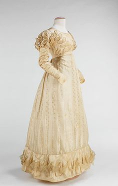 Silk wedding dress, 1824, American. White was not a commonplace color for wedding attire in 1824; until the late 19th century, brides usually wore a colored gown which could be worn again for other social functions after the wedding. A notable feature of this era was the elaborate decoration, 'hem sculpture'. Here the trim is a 3-dimensional leaf pattern incorporating chiffon, repeated on bodice & sleeves.