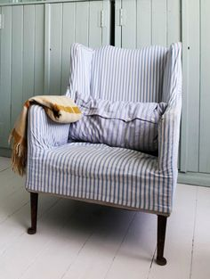 Loose cover on armchair in simple linen ticking.