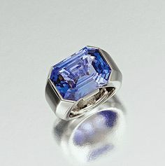 SAPPHIRE AND DIAMOND RING, CARTIER      Horizontally set with a step-cut sapphire, the mount highlighted with two baguette diamonds, mounted in platinum, size 49 ½,     signed Cartier and numbered, French assay and maker's  marks.