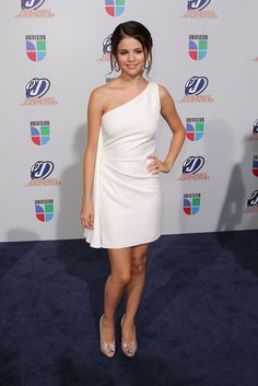 Selena looked fresh and stunning in a one-shouldered white cocktail dress with shimmering pumps.   Brand: Reem Acra