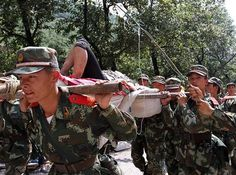 Chinese paramilitary policemen carry an injured victim evacuated from an earthquake hit Zhaotong town, Yiliang County, in southwest China's Yunnan Province, Friday, Sept. 7, 2012.