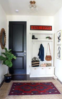 Simple mudroom makeover with layered rugs, a storage locker and black doors to hide hand prints and dirt!