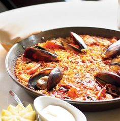 "Paella 101: ""The base of Spain's quintessential dish is always sofrito—tomato, garlic, and onion. Other than that, ingredients vary, because people personalize it. The most traditional in Valencia, Spain, has chicken, rabbit, and a white bean called garrafón, but you'll also find mussels, snails, even lobster."
