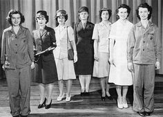 For a publicity photograph, the women of Company H, 2d Headquarters Battalion, Henderson Hall, model the various work and dress uniforms worn by women Marines during the course of World War II. From left are PFC Florence Miller, Cpl Lois Koester, Cpl Carol Harding, Sgt Violet Salela, Cpl Grace Steinmetz, Cpl Rose Mazur, and PFC Mary Swiderski.