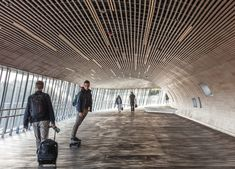 Oakwood was used for the interior of Køge Nord Station to create 'a softer, warmer, more pleasant feeling'. Sustainable Transport, Transport Hub, Aluminium Cladding, Built In Furniture, Bridge Design, Travel Route, Exterior Cladding, Pedestrian Bridge, New City