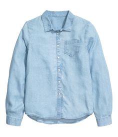 Hellblau. CONSCIOUS. Denimbluse aus weichem, gewaschenem Tencel® Lyocell mit Druckknöpfen vorn und an den Ärmeln. Die Bluse hat eine Brusttasche und einen