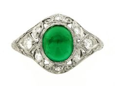 Cabochon emerald and diamond cluster ring, circa 1935. A platinum ring set with one central oval cabochon emerald in a millegrain collet setting with an approximate weight of 2.00 carats, surrounded by a curved pierced bombé frame with integrated shoulders decorated with stylized foliate forms and scrolls and set with eight round old cut diamonds in millegrain bead settings with an approximate total weight of 0.30 carats, all on a tapered half round shank engraved with foliate forms.