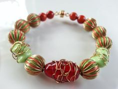 """Made for a SMALL wrist, this bracelet has the playful feel of a carnival atmosphere. The striped metal beads remind me of """"big top"""" tents of travelling circuses.  Shades of red and soft green create a playful energy between the metal and glass beads of different sizes and textures. Tied together with wirewrapped beads, this bead creation will lift your spirits when you wear it. Connected with a strong magnetic clasp, this artful piece is one that you will feel secure wearing for years to…"""