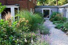 A long border worthy of a grand main garden fits into this transition space between a brick home and its garage. The room effect is enhanced here, thanks to the connecting breezeway. It gives the broad path a destination and accommodates deep planting beds for the textural borders on either side.