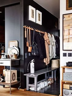 """Entryway inspo: the dark color wall makes the """"true"""" bright interior pop - the coats etc blend into the dark wall. Also like the bench."""