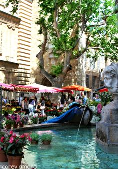 Market stalls by the fountain ~ Aix en Provence , France.  Looks like it would be cooler there than in a typical square.