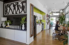 """Tami painted a black accent wall in the living to help camoflauge her television and to make her large second line art piece stand out. The cabinets underneath are from Ikea. """"I love a little storage within the storage space. — an organizing trick. I use this particular piece to organize my office supplies."""""""