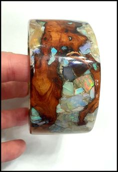A wood and gemstone cuff bracelet by Freestone Peach Designs. This piece features peach wood set with various opals.