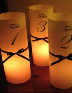 Simple elegance... paper cylinder with table numbers around a votive.  REALLY Pretty with red ribbons! You could use them for your initials on the cake table/guest book...