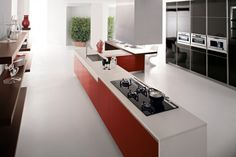Red Kitchen Island With White Corian Worktop And Glossy Black Cupboard With Three Ovens Plus Wood Shelves