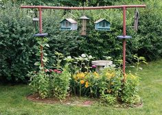 Backyard bird feeder station located in a flower bed dedicated to attracting the birds.