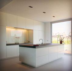 Look total white per una cucina con isola e parete attrezzata. Da notare che i pensili sopra il piano cottura sono fatti a misura e hanno la stessa profondità delle colonne. Di grande effetto il top sp. 6 cm in una tonalità di contrasto.
