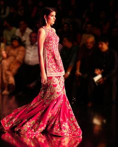 The Sufi Sharara A magnificent assembly of Indian hand-embroidery techniques in multi-color floral jaal motifs with a generous dose of embellishments in the form of minute sequin work lends a breathtaking touch to this fuchsia pink halter neck hand embroidered dupion sharara style. Heavy Dresses, Formal Dresses, Sharara, Sabyasachi, Indian Couture, Indian Dresses, Asian Fashion, Nice Tops, Casual Wear