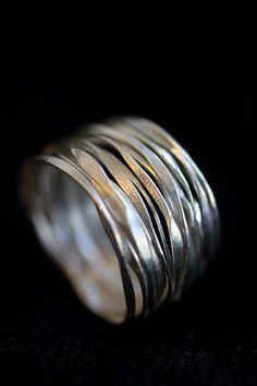 Questo anello unico è realizzato da artigiani Thai in 98% di argento. Il continuo filo dargento è martellato e contorto e poi applicato in 14