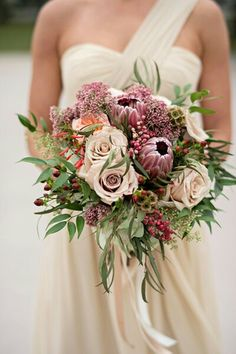 Lovely Wedding Bouquet Arranged With: Dusty Taupe Garden Roses, Peach English Garden Roses, Marsala Queen Protea, Red Hypericum Berries, Red Pepper Berries, Scabiosa Pods, Several Varieties Of Greenery & Foliage