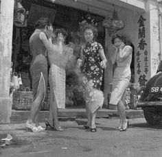 Women in traditional Chinese dress, cheongsam, set off firecrackers to celebrate Chinese New Year