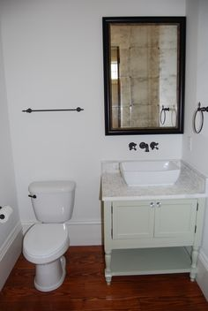 Powder room - custom designed and built vanity, marble tile countertop, vessel bowl sink, wall-mounted oil rubbed bronze faucet, and solid pine wood floors.