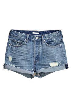 Calções de ganga Trashed: Calções curtos de 5 bolsos em ganga lavada com pormenores de muito desgaste, cintura alta, braguilha de botões e orlas sem acabamento.