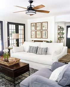 I've always heard that every room should have something black in it to anchor it. These black windows and doors bring drama to this cozy living room. The vintage prints give it a sense of history