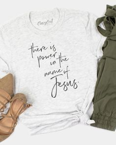 """This is our """"There is power in the name of Jesus"""" design in a vintage black ink on an ash grey tee. We've paired this tee with green bottoms and some close-toed sandals for a super comfy and casual look! Christian Clothing, Christian Shirts, Christian Apparel, Cute Tshirts, Cool Shirts, Pretty Shirts, Cute Shirt Designs, Game Day Shirts, Jesus Shirts"""