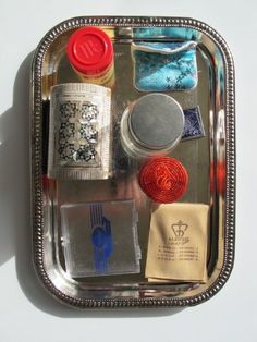 Include a bag with a velcro open/close, an open/close tie, a bag with a snap open/close, a box with a small button to push to open/close, a plastic spice container with a flip open/close, and a plastic container with a somewhat complicated open/close along with an assortment of jars and bottles.  Read more at:  http://carrotsareorange.com/montessori-in-the-home-open-and-close-tray/