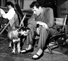 "Errol Flynn with his schnauzer Moody on the set of ""Never Say Goodbye"" in 1945."