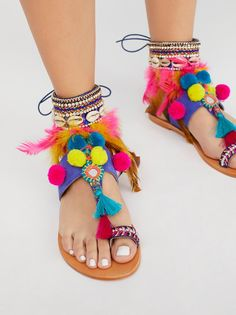 Milos Embellished Sandal   Colorful and overly embellished sandal accented with embroidery, beads, rhinestones, shells, pompoms, and feathers.   * Adjustable ankle strap * Toe loop