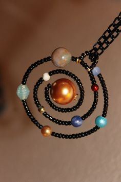 Solar system necklace. That is gloriously geeky. I love it! :)(would it be considered cheating to wear it to science class on test day?)