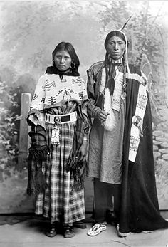 Standing studio portrait of two Native Americans (Ute), Julian Buck and his wife. She wears a beaded shawl over a dress with a beaded belt and bag. He wears a long shirt,