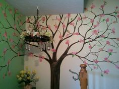I wish I could put this tree in my house. She painted it on the wall. The flowers are fabric stuck on with starch... so she can change the leaves/flowers/fruit/icicles/snow? for the season.