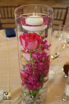 Add water and floating candles to a cylindrical vase of flowers for a center piece that is sure to demand attention.