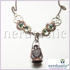 """Steampunk Gear Necklace, Lantern Necklace, Mixed Metal, Cosplay Jewelry, Costume Accessories, Geekery, Nerd Gifts, Copper Jewelry    The focal point of this industrial design is a bronze colored lantern.      The lantern hangs from a copper tone bar that is fixed to a series of gears.  Four gears feature a glass, green cube bead.    The necklace measures approximately 20"""" and is composed of nickel free chain.  The close is a lobster clasp.    One of a kind item.    -----  ▼Free US Shipping…"""