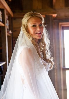 Brides.com: A bride in a Monique Lhuillier wedding dress and veil | Photo credit: Randy Barnes